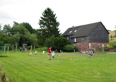 Vor dem Hof lädt eine große Rasenfläche zum Toben und Ballspielen ein. Für kleinere Kinder gibt es Sandkasten und Klettergerüst.
